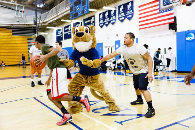 uedbet Cougar playing basketball with students