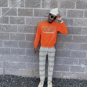 Kean student models orange sweatshirt and plaid